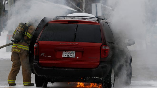A red Dodge minivan is on fire at the intersection of Custer and 39th Streets early afternoon on Thursday, Feb. 18.