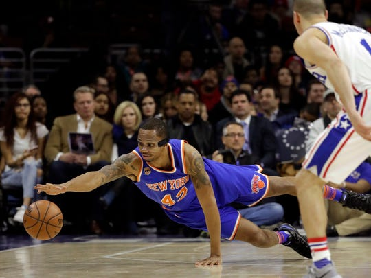New York Knicks' Lance Thomas, left, dives for the ball as Philadelphia 76ers' TJ McConnell looks on during the first half of an NBA basketball game, Friday, March 3, 2017, in Philadelphia. (AP Photo/Matt Slocum)
