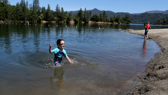 Ethan True, 3, left, and his brother Nolan, 5, swim Monday at Brandy Creek Beach. The boys and their family had traveled from Denver, Colorado, on Saturday, where it was 30 degrees. They are visiting their grandparents in Redding.