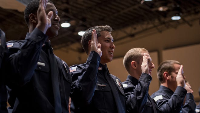 Paul Kieu/The Advertiser New firefighters recite the oath of office Friday during the Lafayette Fire Department?s graduation ceremony at the Clifton Chenier Center. New firefighters recite the oath of office during the Lafayette Fire Department's 98th Firefighter Academy Graduation at the Clifton Chenier Center in Lafayette, La., Friday, Feb. 27, 2015.