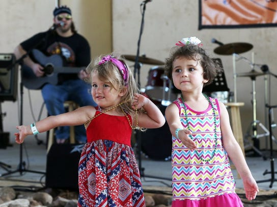 Marylin, 3, and Isabella, 4, dance as a musician performs