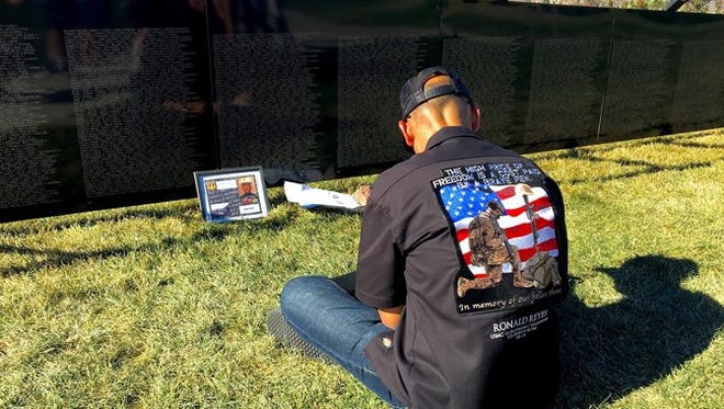 A man sits beside the mobile replica of Vietnam Veterans Memorial to honor the more than 58,000 American service men and women who fell in the Vietnam War. The Wall That Heals will make a stop in Yancey County in October.