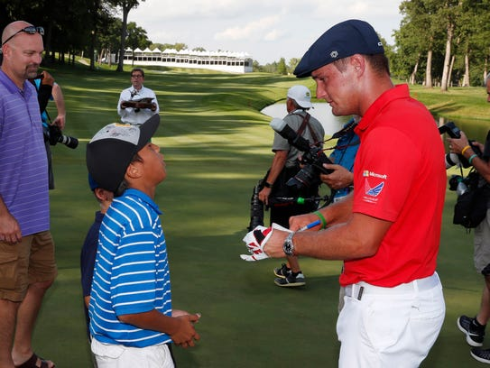 Bryson DeChambeau autographs his glove for a young