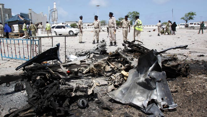 Somali soldiers stand near the wreckage of a suicide car bomb near the Somali parliament in Mogadishu, Somalia on July 5.