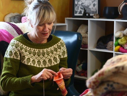 Ency Austin knits a sock at her home in Red Hook wearing a sweater she made designed by Isabell Kraemer.