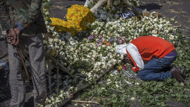 An Ethiopian relative of a crash victim mourns and grieves next to a floral tribute at the scene where the Ethiopian Airlines Boeing 737 Max 8 crashed shortly after takeoff on Sunday killing all 157 on board, near Bishoftu, south-east of Addis Ababa, in Ethiopia Friday, March 15, 2019.