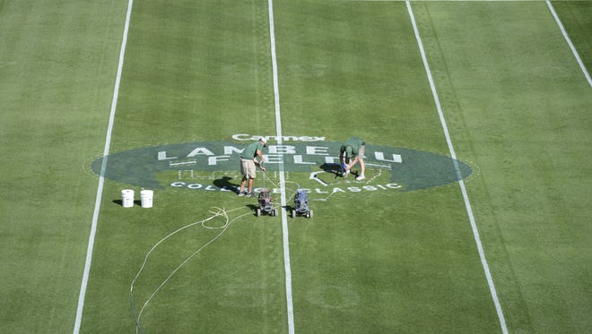 Green Bay Packers ground crew members paint the Lambeau Field College Classic at midfield Thursday.