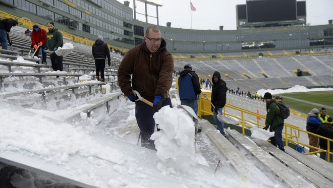 Tom Loch of Suamico shovels snow at Lambeau Field on Monday. The Packers appealed to the public to clear the stadium for Saturday's game against the Minnesota Vikings.
