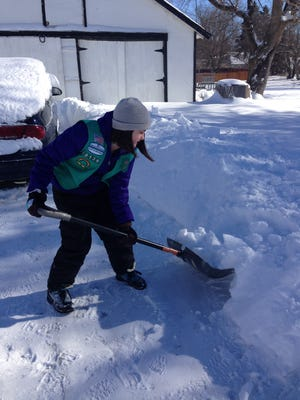 Kaylee Nickel of Charlotte decided to shovel snow Monday to earn credit for a Girl Scout badge.