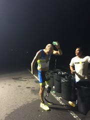 Double amputee and local attorney Jason Gunter gets some water and an aid station during the run portion of the Ironman World Championships in Kona, Hawaii. Hunters prosthetic leg had to be replaced because of a malfunction.