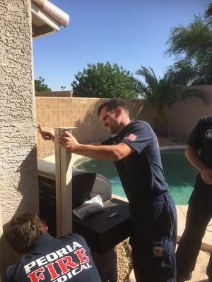 A Peoria Fire and Medical Department crew fixes a family's broken pool fence on Thursday afternoon.