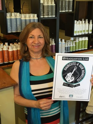 Zine Gallo Brechbill, owner of Enza's, An Organic Salon in downtown Salisbury holds a flyer for a May 15 event she organized that will provide free haircuts to area homeless.