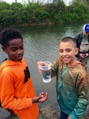 Jayden Jewell, 10, and Jordan Heroux, 9, release trout into the South River on Saturday during Riverfest. The two boys are students at Spratley Gifted Center in Hampton.