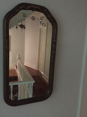 A vintage mirror accents a redone stairway.