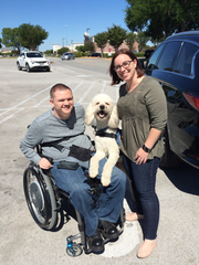 Stephen and Erin Willoby pose for a photo with K.C., a goldendoodle service dog. Stephen Willoby, an Air Force veteran and explosive ordnance disposal technician who lives in Waddell, Arizona, received the dog through a partnership between the EOD Warrior Foundation, based out of Niceville, Florida, and the MADE in Texas Assistance Dogs group in Grand Prairie, Texas.