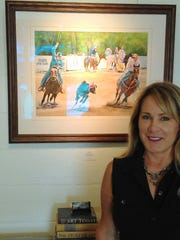 Lana Shepherd stands beside the painting she did of her husband in action as a team roper.