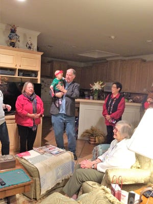 Jan Lassiter, seated, listens to the carols sung for her at a stop by the 35th annual STER caroling party. Standing, from left, are Liz Hernandez, First United Methodist Church senior pastor Scott Bradford holding baby Lucille Baxter, and Ofelia Gonzales.
