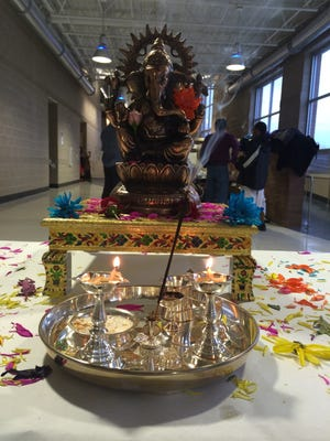 A bronze statue of the Hindu god Ganesha welcomed visitors to the 2015 Harvest Festival Saturday at Clear Creek Amana High School in Tiffin. Many in attendance stopped at the statue to pray as they walked through the festival.