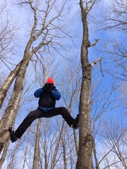 """Filmmaker Aaron Peterson climbs to get a view for """"The Michigan Ice Film."""""""