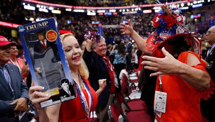 Florida delegates Dana Dougherty, left, holding a Donald Trump doll and Kat Gates Skipper dance before the start of the third day session of the Republican National Convention in Cleveland, Wednesday, July 20, 2016. (AP Photo/Mary Altaffer)
