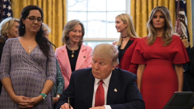 President Trump signs a bill to encourage women to study science and engineering in the Oval Office Tuesday.