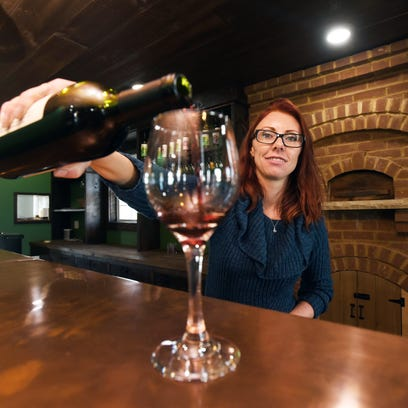 Camieo Adams pours a glass of wine at Vinberige Vineyards
