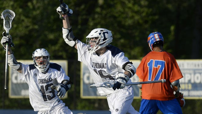Webster Thomas' Colin Horan, center, celebrates his game-winning goal with Joe Luconte during a regular-season game against Penn Yan, a 9-8 Titans' victory in double overtime.