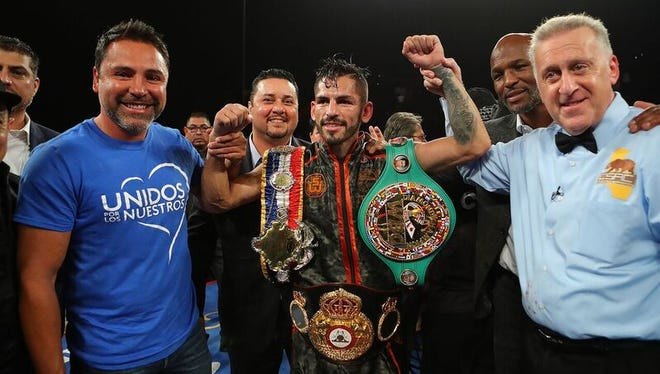 Jorge Linares, center, gets his hand raised by referee Jack Reiss after his victory Saturday night.