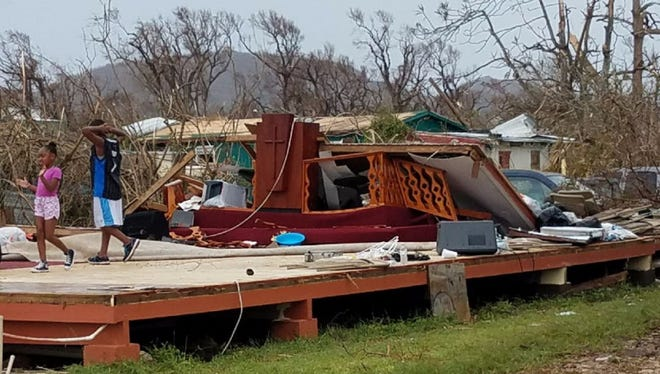 St. Croix residents survey the ruins of a church last week. Hurricane Maria slammed the tiny territory in the U.S. Virgin Islands last week, leaving residents without power.