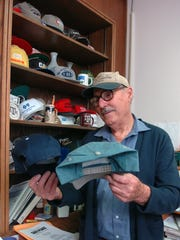 Willie, administrative assistant to the Wichita County Judge, looks over his collection of caps