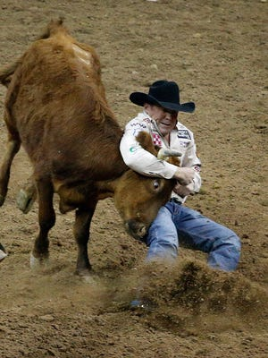 K.C. Jones takes down a steer in 3.4 seconds for a first place finish in the steer wrestling event during the first go-round of the National Finals Rodeo Thursday, Dec. 3, 2015, in Las Vegas.