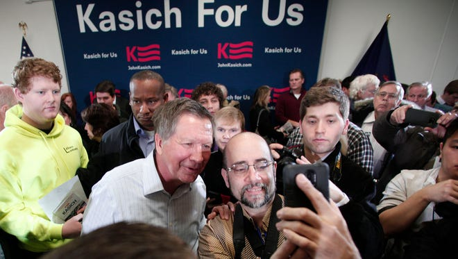Ohio Governor and Republican Presidential Candidate John Kasich poses for a photo after he held a Town Hall meeting in Livonia, Michigan.