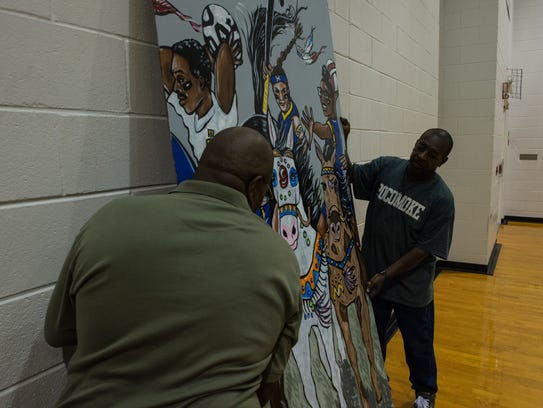 Michael Rogers and Paige Conquest place a mural in