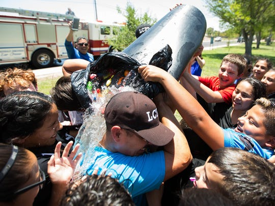 Jaime Montoya, Las Cruces Police Chief, gets a bucket of water dumped on him by the campers at the LCPD Youth Leadership Summer Camp after a water balloon fight between campers and officers Thursday, June 29, 2017, at Young Park.