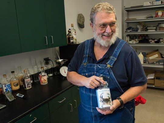 Tom Cropper, owner of Spirits of Patriots, holds a concept bottle label at his Princess Anne distillery on Monday, Nov. 13, 2017.