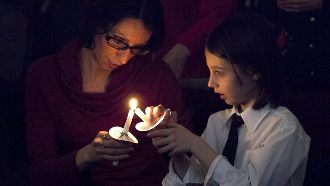 Candles are lit during Christmas Eve services at Heart of the Rockies Christian Church in Fort Collins last year.