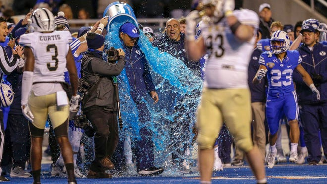 BYU coach Kalani Sitake is doused at the end of the team's 49-18 win over Western Michigan in the Famous Idaho Potato Bowl NCAA college football game Friday, Dec. 21, 2018, in Boise, Idaho. (AP Photo/Steve Conner)