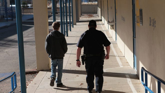 """FILE - In this Dec. 9, 2013, file photo, a school resource officer in Anderson, Calif., walks a middle school student back to class. Portland Public Schools, Oregon's largest school district, will discontinue its use of Portland Police Bureau school resource officers. Superintendent Guadalupe Guerrero said Thursday, June 4, 2020, the district needed to """"re-examine our relationship"""" with the police in light of the nationwide upheaval over the death of George Floyd."""