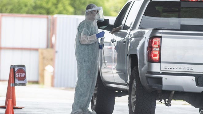 A health worker at the Austin Emergency Center in South Lamar Boulevard performs a COVID-19 test at the drive-thru test site on Sunday.