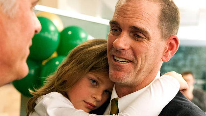 New CSU football coach Mike Bobo and his youngest daughter, Kate, are pictured at Bobo's introductory press conference Tuesday. Bobo and his wife Lainie have five children.