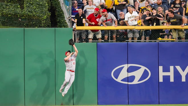 Cincinnati Reds right fielder Scott Schebler (43) catches a fly ball at the fence from Pittsburgh Pirates right fielder Gregory Polanco (25) during the fifth inning at PNC Park.