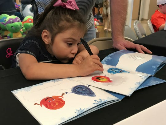 Jenna Reeves, 4, signs her name on a page in the book