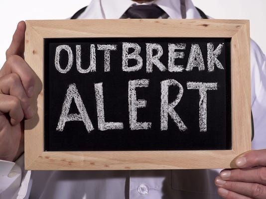 Outbreak alert text written on blackboard in doctor hands, epidemic warning