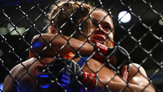 Amanda Nunes (right) hugs Ronda Rousey following their fight during UFC 207 at T-Mobile Arena.
