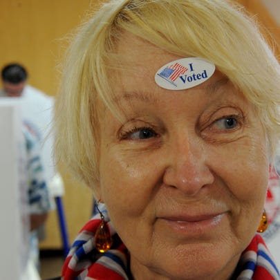 Delilah Orloff puts the I Voted sticker on her forehead