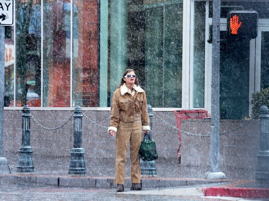 A woman waits for the light change to cross the street in downtown Reno as a light but steady snow falls Thursday, Feb. 22, 2018.