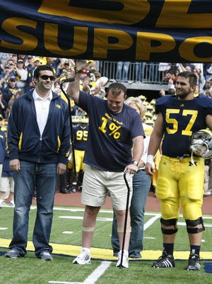 Car crash victim Brock Mealer, center, flanked by his brothers Blake, left, and Elliott at Michigan Stadium in Ann Arbor on Sept. 4, 2010.