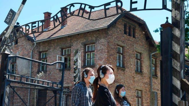 "Visitors are seen near the gate with its inscription that translates as ""Work sets you free"" at the memorial on the site of the Auschwitz death camp set up by Germany during World War II, in Osweicim, Poland, on July 1, 2020. The memorial reopened to visitors this summer after being closed due to the COVID-19 lockdown."