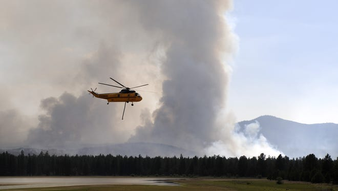 In a Sunday, June 8, 2014 photo, two helicopters ferry water from near Tumalo Reservoir to the Two Bulls Fire area, fire about 1.5 miles away. About 50 households northwest of Bend were under evacuation notices on Monday after two weekend fires started near Tumalo Reservoir and joined to burn in an area of about 10 square miles, more than 6,000 acres. The fire posed a threat to hundreds of homes in rural subdivisions as well as the city's water supply.
