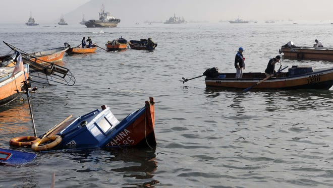 Fishing boats lie damaged by a small tsunami, in the northern town of Iquique, Chile, after magnitude 8.2 earthqauke struck the northen coast of Chile, Wednesday.